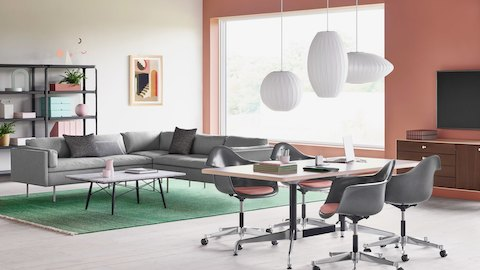 A brightly lit lounge setting with Eames Task Chairs, Bolster Sofas, and Steelwood Shelving. Select to learn more about The Herman Miller Collection at work.