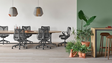 A Y base Headway conference table surrounded by seven Cosm chairs in an open conference space with a Headway communal table with stools nearby.