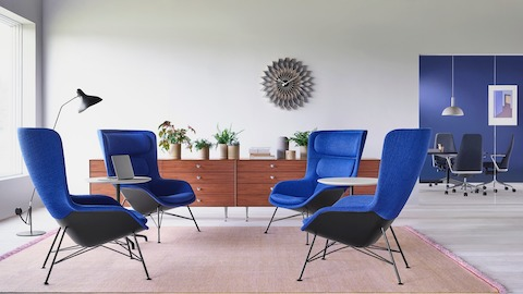 A casual setting featuring four blue Striad Lounge Chairs with two Striad Tables between them. Select to learn more about Collection at Work.