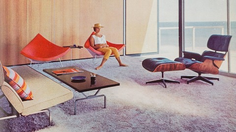 A woman sits in one of a pair of orange-pink Nelson Coconut Chairs in the sunny living room of a mid-century modern home in Malibu. An Eames Lounge Chair and Ottoman and Eames Sofa Compact are nearby.