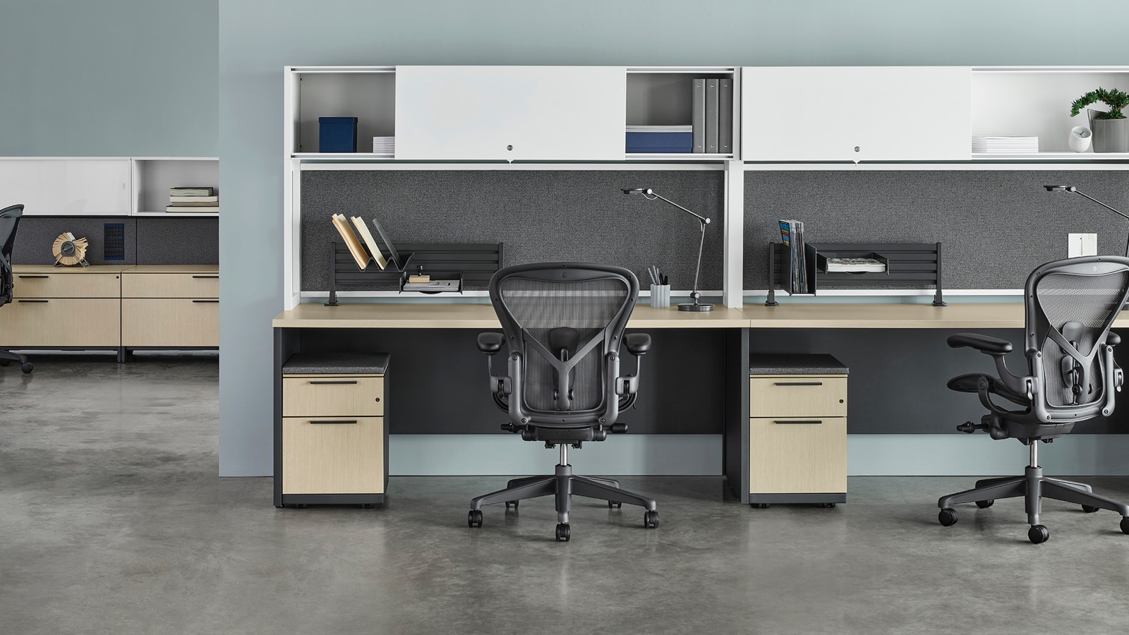Three Canvas Metal Desks with white upper storage, gray fabric back panels, and light wood surfaces with another workstation in the background, all with dark grey Aeron chairs.