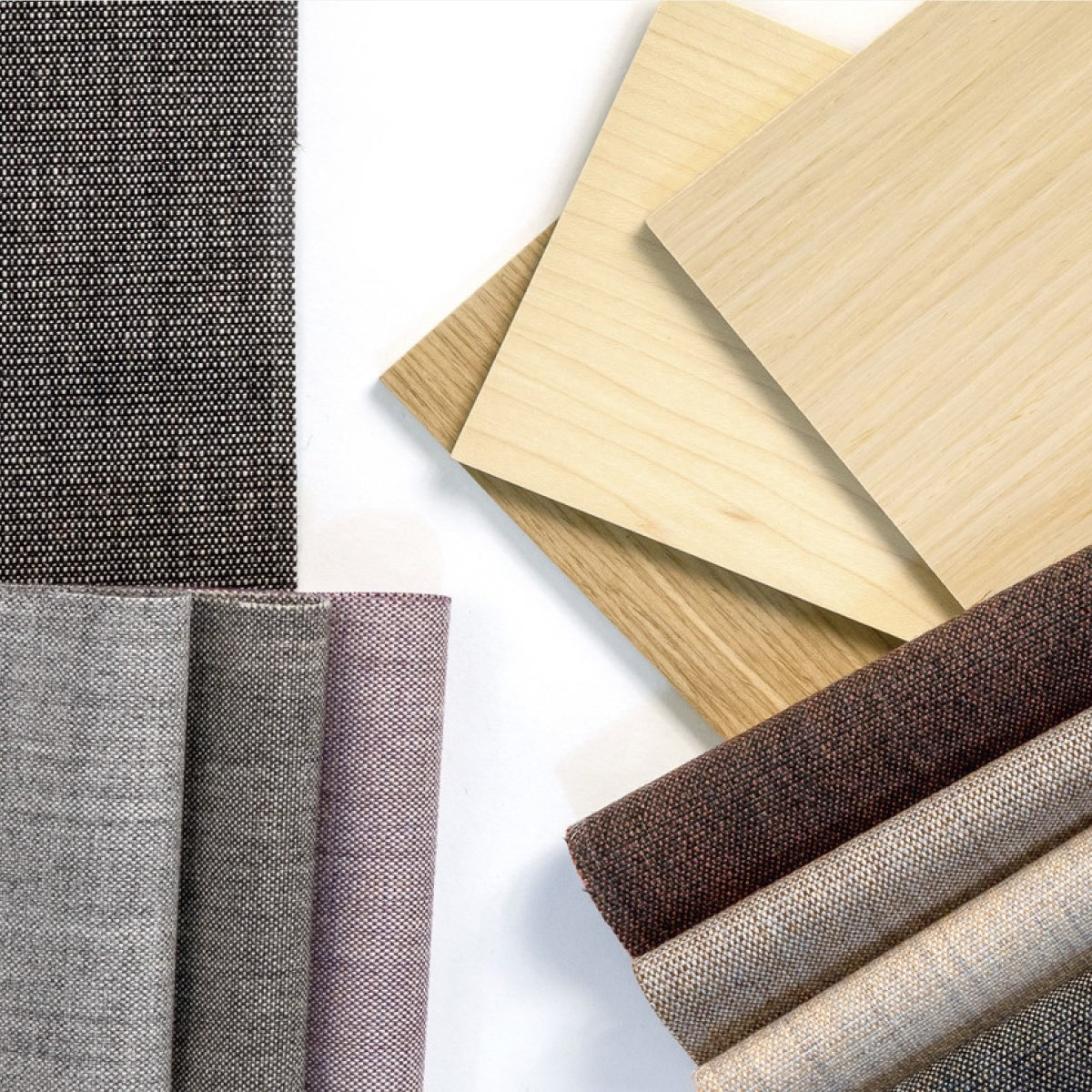 An overhead view of a variety of material samples including fabrics, and laminates in a range of colors.