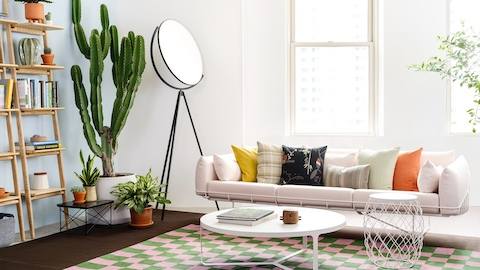 A light pink Wireframe Sofa with assorted throw pillows in solids and patterns sits on a checkered green and pink rug. Nearby are white round coffee and wire side tables and wooden open bookshelves leaning on the wall. Select to learn more about Herman Miller at NeoCon.