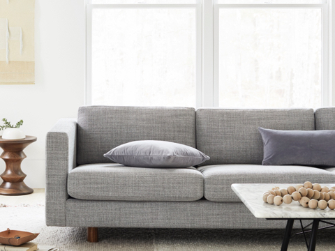Grey Lispenard Sofa with marble Eames Coffee Table and Eames Walnut Stool.