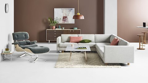 Open lounge with a light gray Lispenard sofa sectional next to an Eames marble top coffee table and an Eames Lounge Chair with gray mohair upholstery. Select to go to the Lispenard product page.