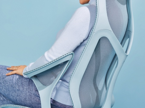 A woman reclining in a Glacier light blue Cosm high-back ergonomic office chair.