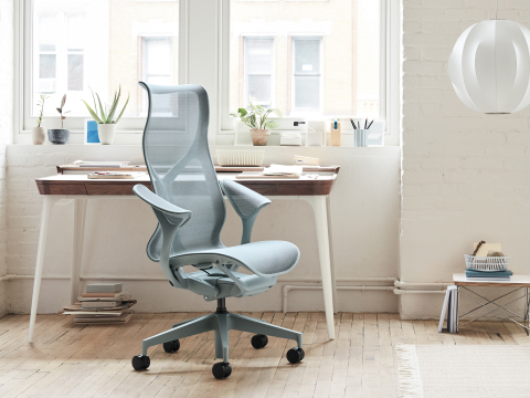 A blue Cosm office chair sitting in front of a white desk and a bright, sunlit window.